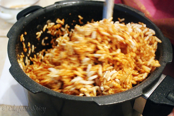 The jaggery solution is mixed with white sesame seeds, coconut scrapings and dry ginger powder, and the mixed with the puffed rice